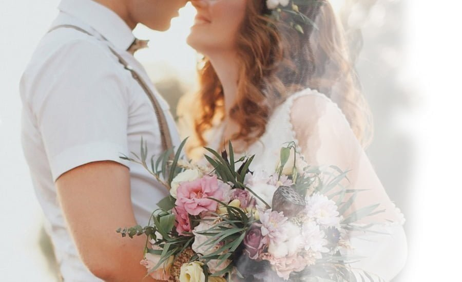 Bride and groom touching noses, wife holding a wildflower bouquet